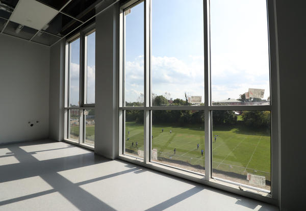 Interior of the new academic building, looking out from windows into the field