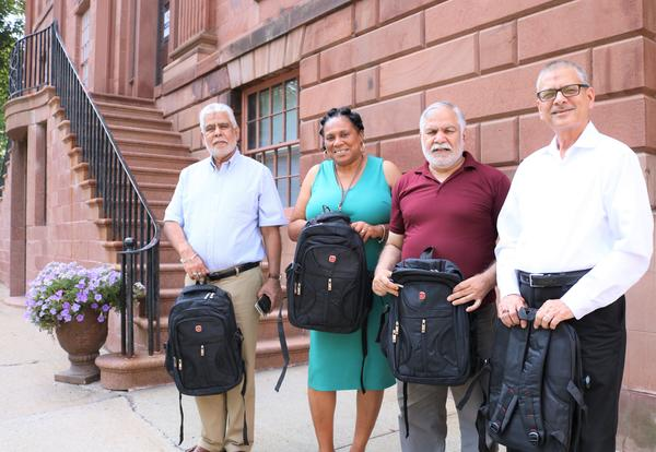 Community partners pose outside Academy Park with donated backpacks.
