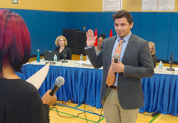 New board member Hassan I. Elminyawi being sworn in at the Sept. 12 meeting.