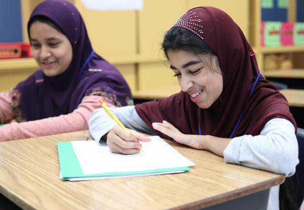 Two students smiling while working on math problems at their desks.