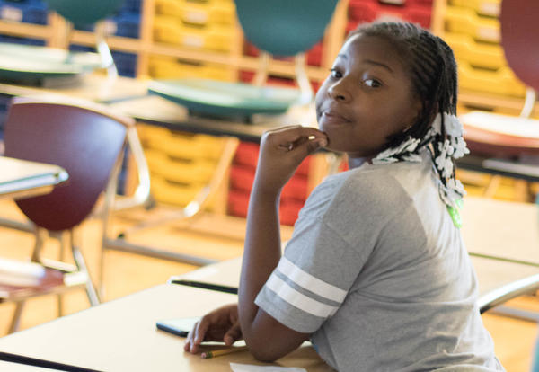 Student sits at her desk during open house.