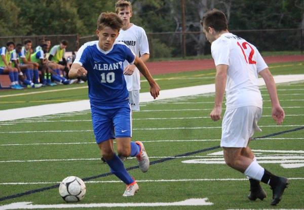 Albany High soccer team playing an opponent on the field.