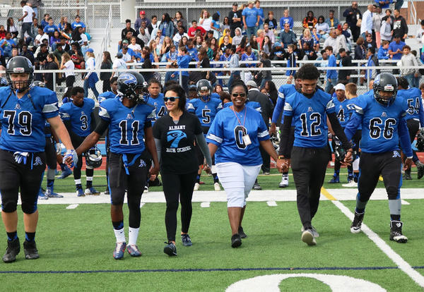 Superintendant Kaweeda G. Adams, Albany High Principal Jodi Commeford and varsity football players walk hand-in-hand prior to the 2018 Homecoming game.