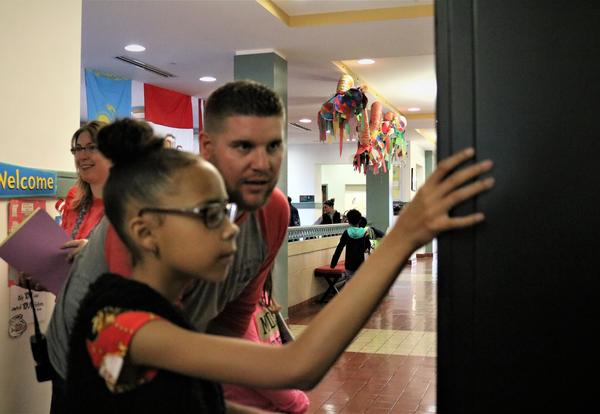 Assistant Principal Glenn Westfall helps a student choose a book from the ASH book vending machine.