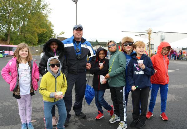 Grade 3 students pose with an Albany Police Officer at CDTA's Fall Festival.