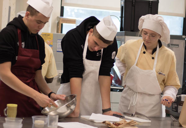 Two boys and a girl mix ingredients in the Abrookin kitchen