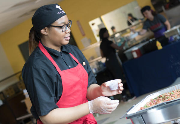 Student dishes up a serving a chili