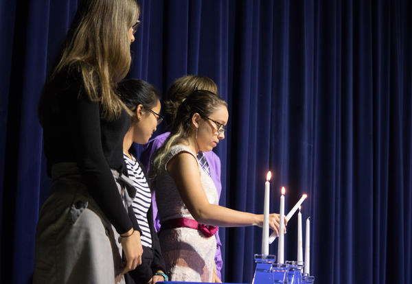 Students lighting ceremonial candles during the National Honor Society Induction.