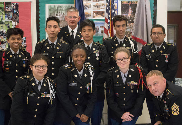 JROTC students in uniform stand with their supervisors