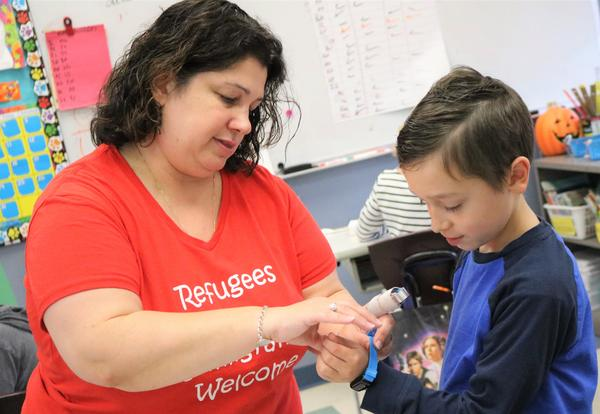 A teacher helps a third-grader put on his activity tracker bracelet.