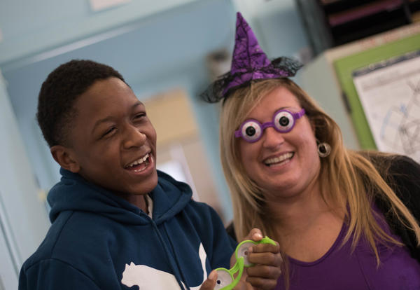 Student and teacher laughing while wearing silly glasses