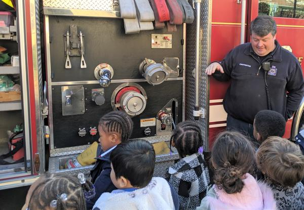 A member of the Albany Fire Departments teaches students about the fire truck.