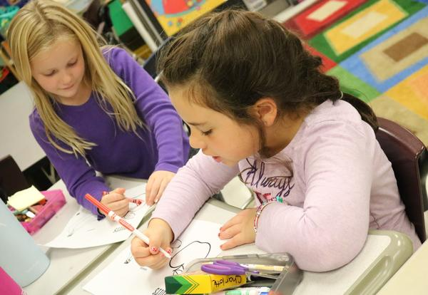 Two girls use markers in a third-grade classroom.