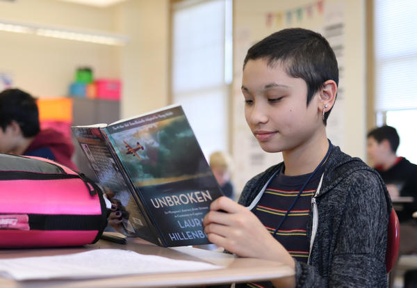 Student reading a book at their desk.