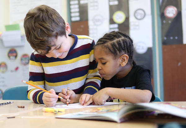 Two students working at their desk, reading and writing.