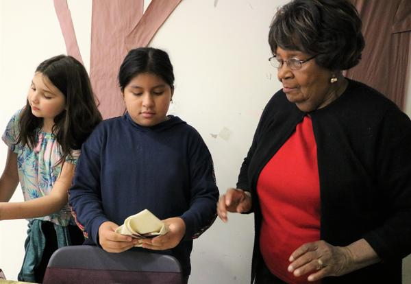 A lunch aide teaches a sixth-grader how to correctly fold a napkin.