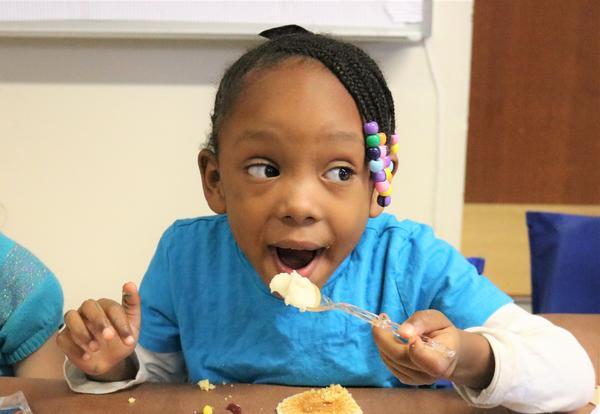 A kindergarten student enjoys a plate full of Thanksgiving food.