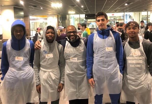 Coach Sean Brown and members of the boys' basketball team volunteer at Equinox Thanksgiving dinner prep.