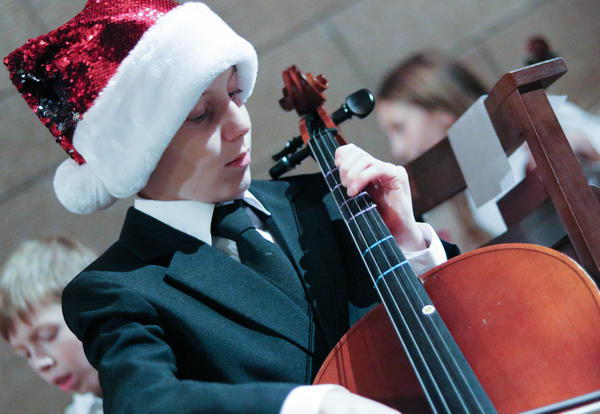 Student wearing a santa hat plays cello