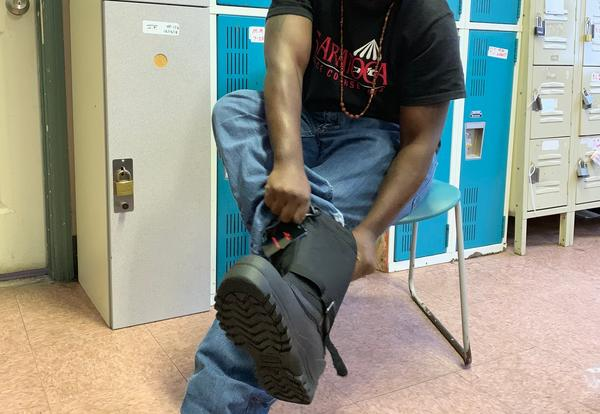 A man tried on a pair of winter boots donated by Stephen and Harriet Myers Middle School staff.