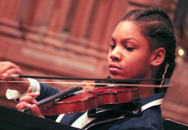Girl plays violin at 1st Friday concert