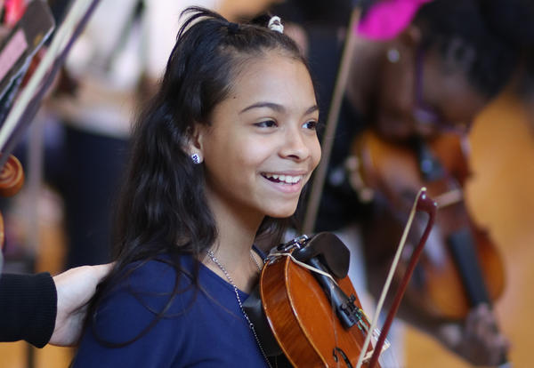 Student smiling with their violin during the winter concert performance.