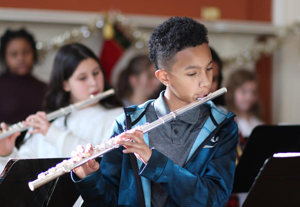 Student playing the flute during the performance at Academy Park.