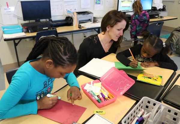 A teacher and two students create Christmas cards.