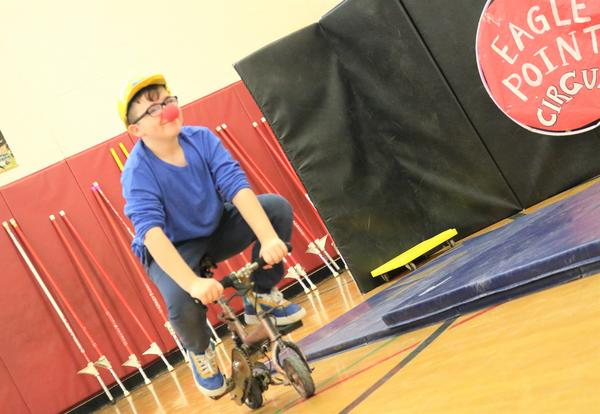 A student rides a tricycle with a clown nose.