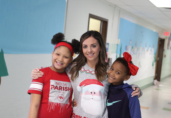 Two students posing for a picture with their teacher.