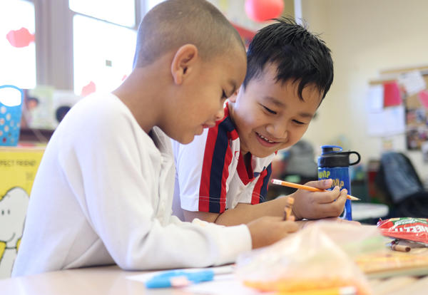 Two smiling boys work together on a writing project.