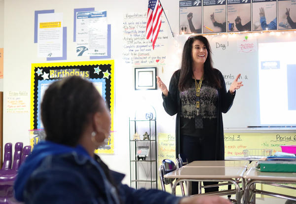 Teacher stands in front of classroom and student