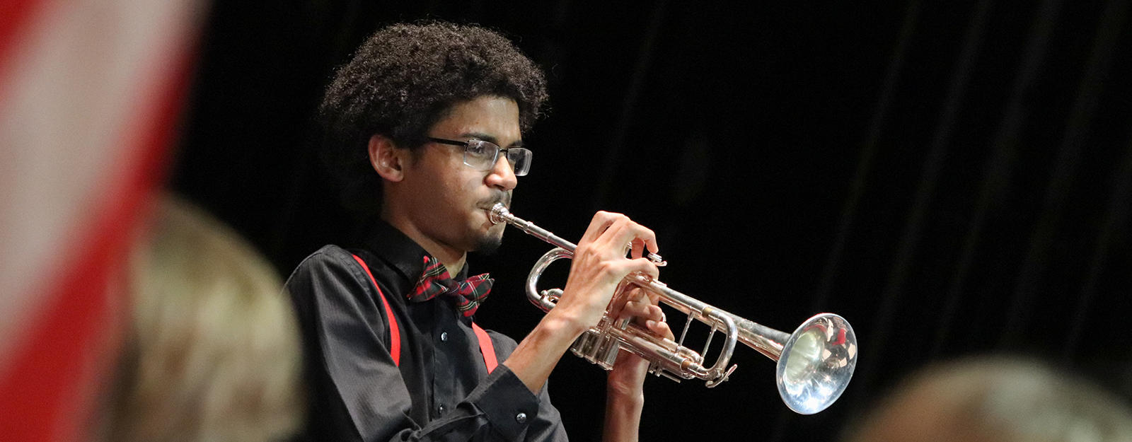 Student playing a trumpet during a concert.