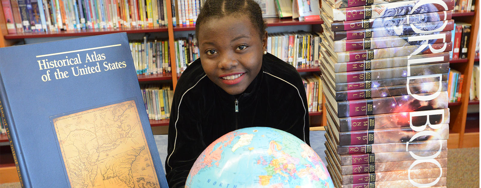 Student smiling behind a globe and stack of history textbooks.