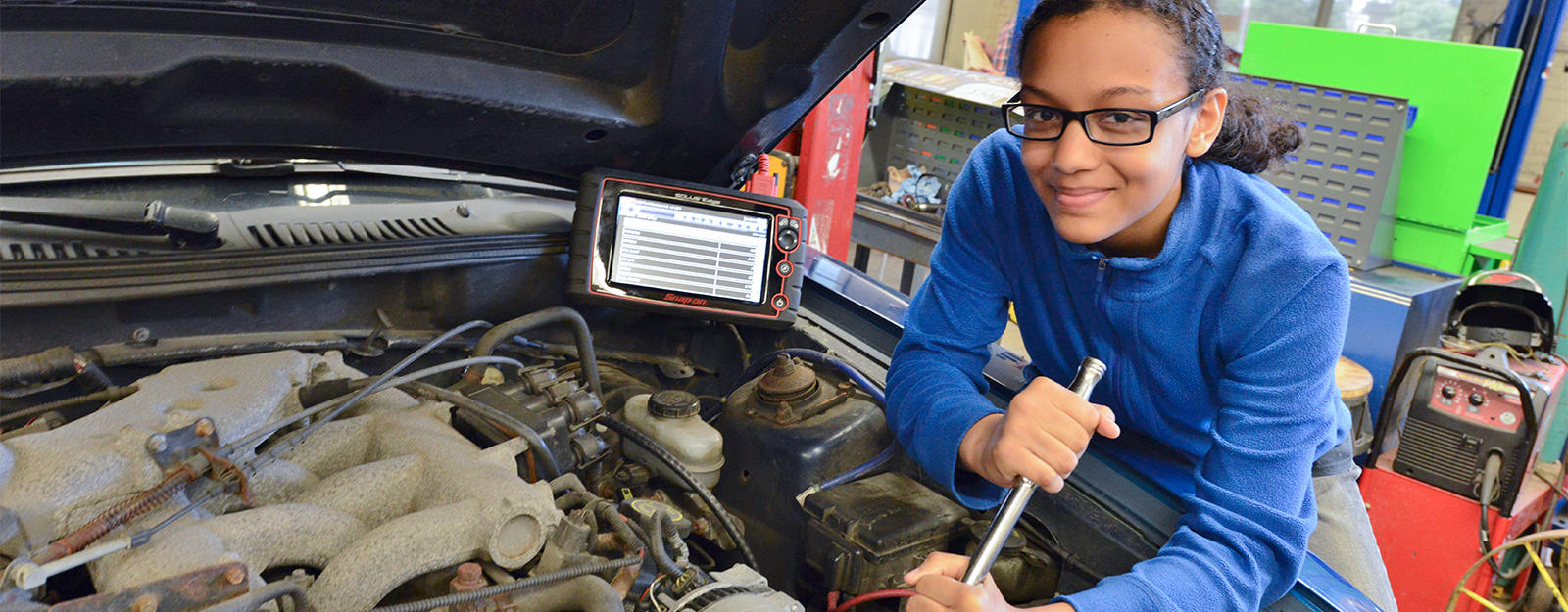 Student working on the engine of a car.