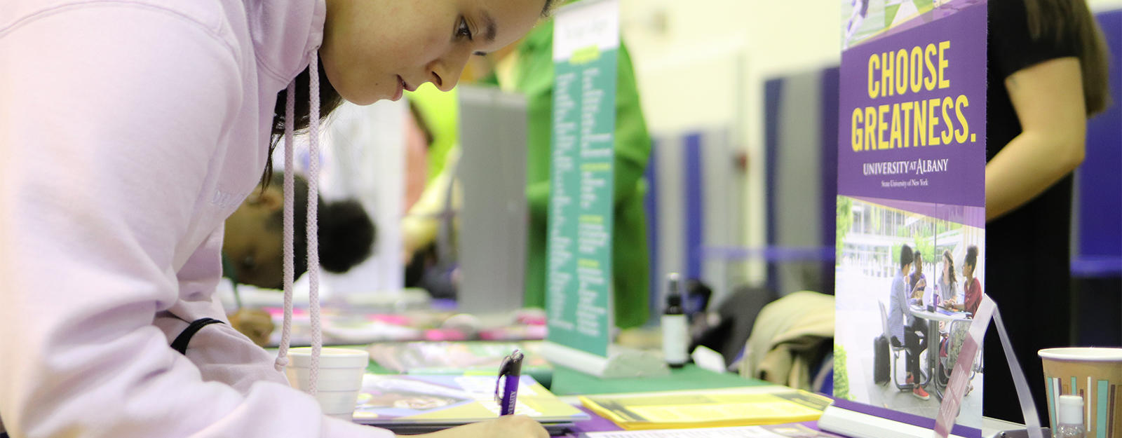 Student filling out paperwork at a SUNY Albany table during a college fair.