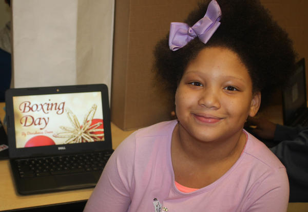 Smiling girl shows off a presentation she made on her laptop.