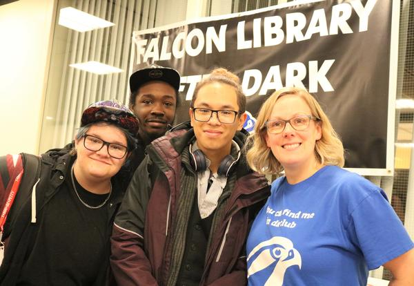 Albany High librarian poses with students during Falcon Library After Dark event.