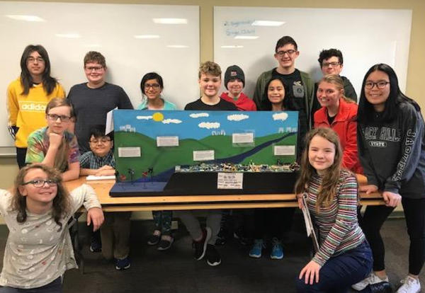 Girls and boys in the Hackett Middle School STEM Club pose with their Future Cities project.