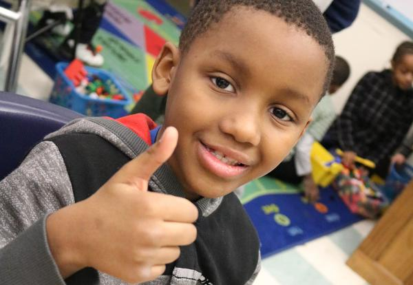 A Giffen Elementary student gives the thumbs-up sign after sampling macaroni and cheese for a fundraiser.