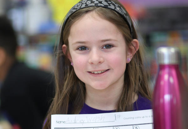 Student holding up math work.