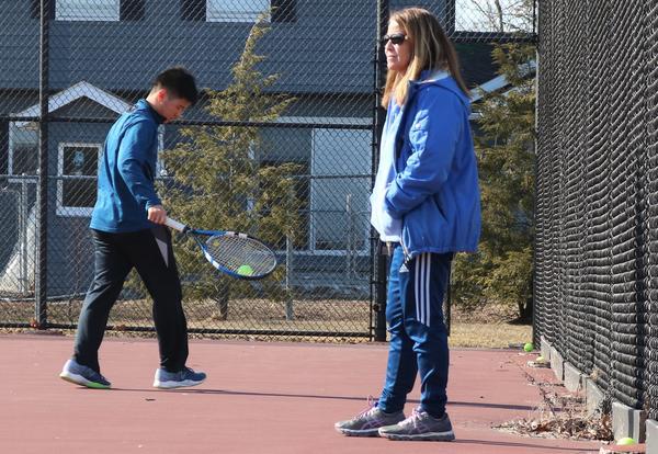 Marianne Leung observes a boys' tennis practice.