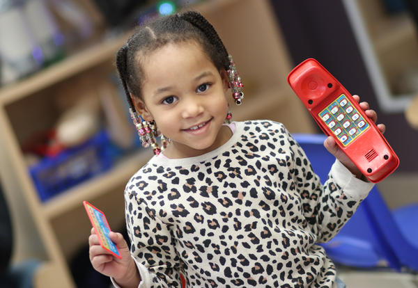 Pre-K girl operates a play telephone