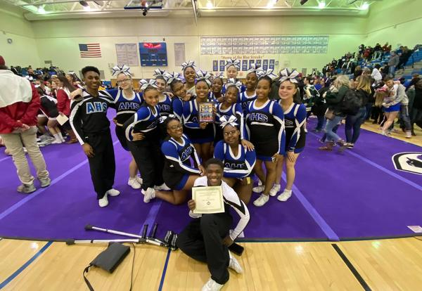 The varsity cheerleading team poses at a competition.