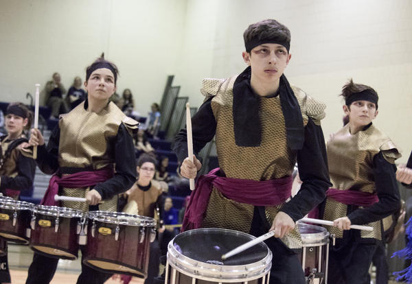 Three costumed students play drums