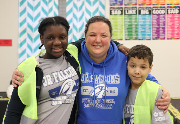 Reading teacher Victoria DeGouff and two students posing for a photo.