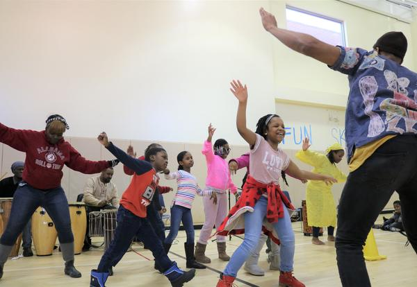 Students learn how to dance during an assembly.