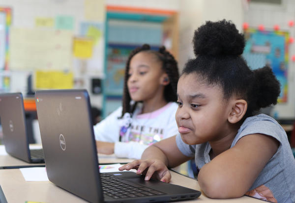 Two students doing math work on Chromebooks.