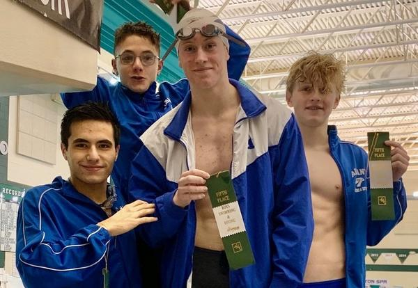 Four members of the boys' swim team show their ribbons