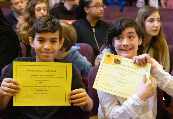 Two Hackett students hold up their honor roll certificates